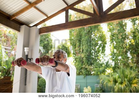 Senior man exercising with dumbbells under shed in yard