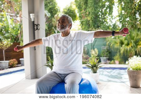 Senior man with arms outstretched lifting dumbbell while exercising in yard