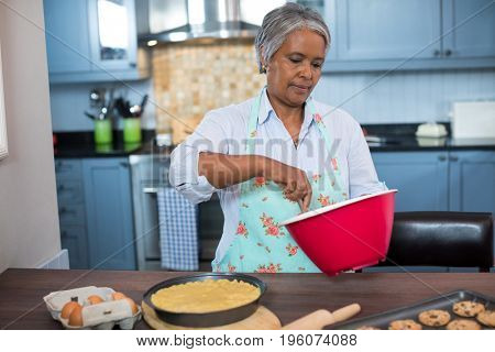 Senior woman preparing food while standing in kitchen at home