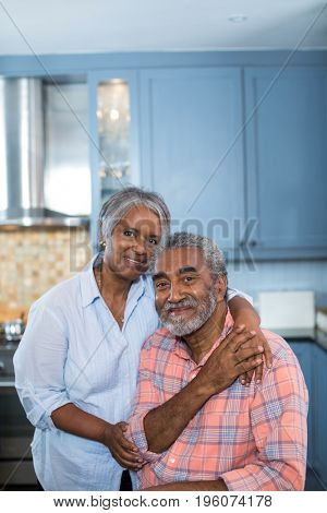 Portrait of smiling couple with arm around in kitchen at home