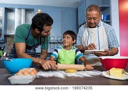 Man using table while standing by father and son preparing food in kitchen at home