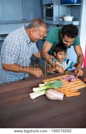 High angle view of man looking at boy cutting onion with father in kitchen at home