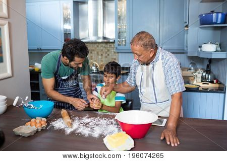 High angle view of family preparing food while standing in kitchen at home