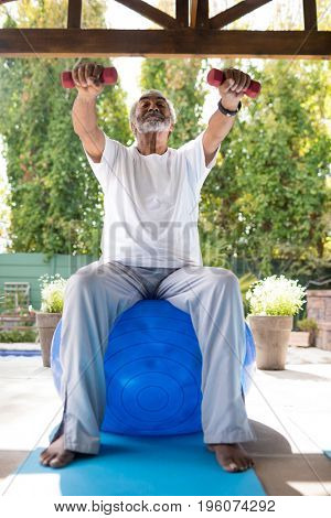 Full length of man exercising while sitting on fitness ball under shed in yard