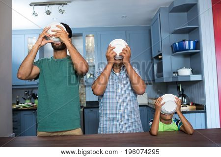 Family having breakfast while standing at table in kitchen