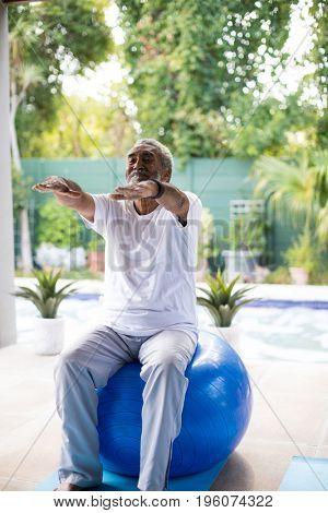 Senior man exercising while sitting on fitness ball yard