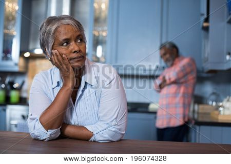 Thoughtful woman with man in background at home