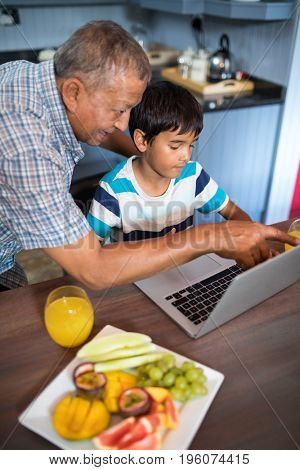 Grandfather assisting grandson using laptop in kitchen at home
