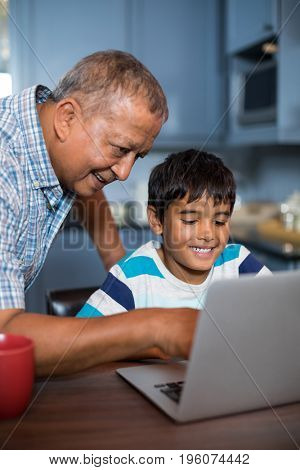 Smiling grandfather assisting grandson using laptop in kitchen at home