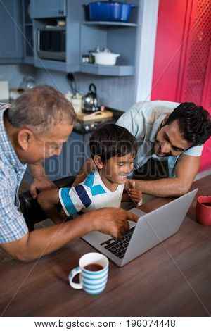 High angle view of happy father and grandfather looking at boy using laptop