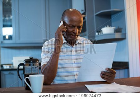 Man reading document walking talking on phone in kitchen at home