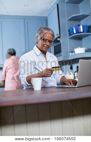 Smiling woman using credit card while doing online shopping at home