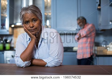 Woman with hand on chin leaning on table in kitchen