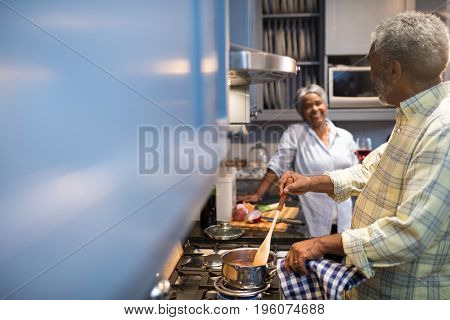Couple talking while preparing food in kitchen at home