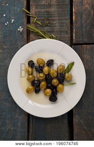Overhead view of olives in plate with oil on wooden table