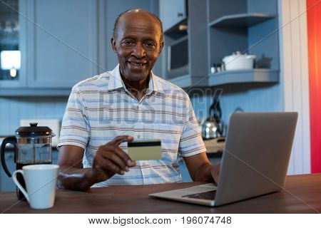 Portrait of man holding credit card while using laptop at home