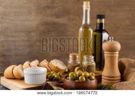 Olives with pepper shaker and oil bottles by bread on table against wall