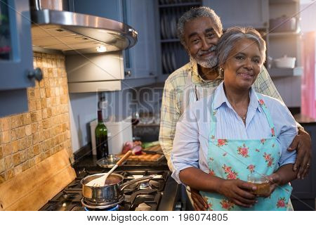 Portrait of couple standing by stove in kitchen at home