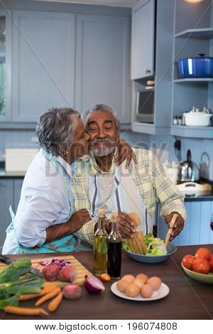 Side view of woman kissing man while preparing food in kitchen at home