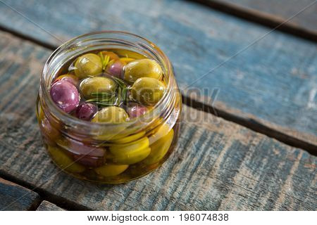 Close-up of marinated olives in jar on wooden table