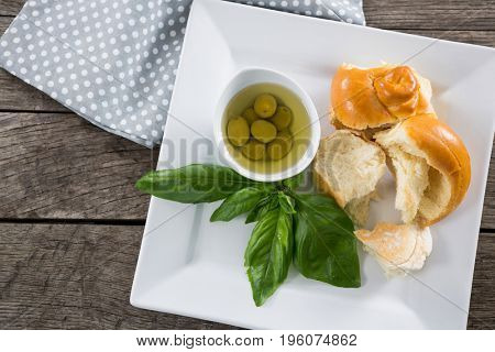 Pickled olives with herbs and bread in platter on wooden table
