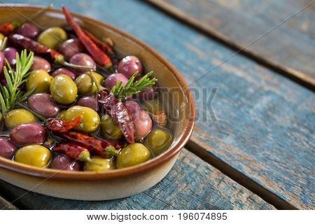 Close-up of pickled olives in bowl on wooden table