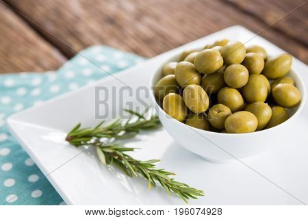 Close-up of marinated olives with rosemary on tray
