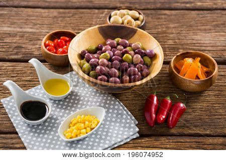Marinated olives with various ingredients on wooden table