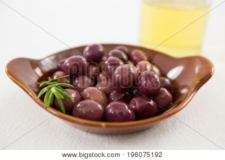 Close-up of marinated olives in bowl on white background