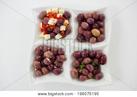 Marinated olives with herbs and spices on white background