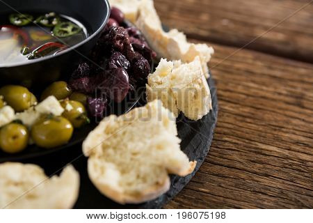 Close-up of pickled olives and vegetables surrounded with bread pieces