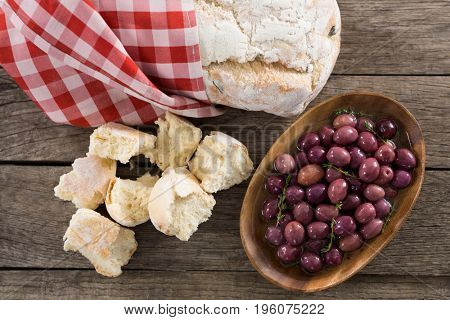 Marinated olive with bread loaf on wooden table