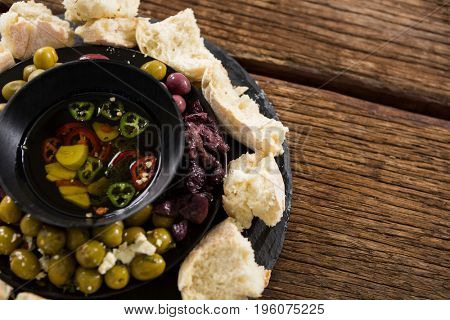 Pickled olives and vegetables surrounded with bread pieces on plate
