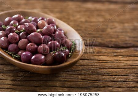 Marinated olives in wooden bowl on table