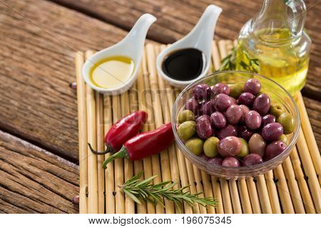 Marinated olives with ingredients on wooden table