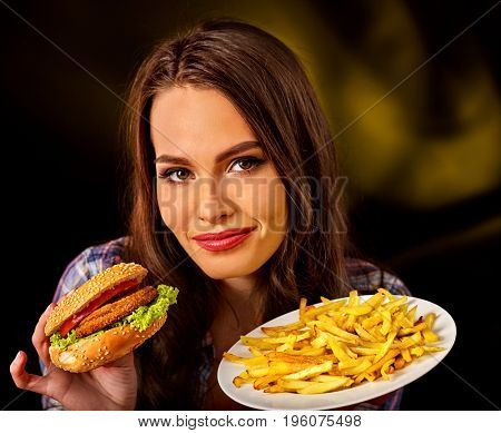 Woman eating french fries and hamburger. Student consume fast food on table. Advertise fast food on dark background. Use of semi-finished products because of unwillingness to cook.