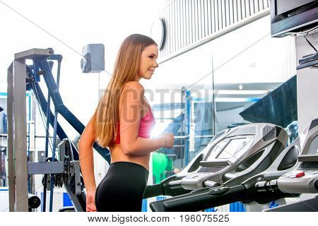 Fitness woman workout in jogging on treadmill gym. Girl working on waist twisting disc. She looking away sport indoor.