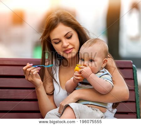 Baby feeding spoon by mother in park outdoor. Weaning in first weeks. Eating child summer on bench. Good appetite by baby food with foster mother number one. Color tone on shiny sunlight background.