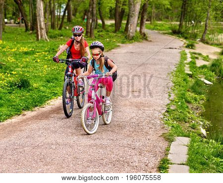 Mother and daughter on bicycle. Bikes cycling family. Happy mother teaching daughter to ride bike. Kid practice to riding lady bicycle. Friendship between children of different ages.