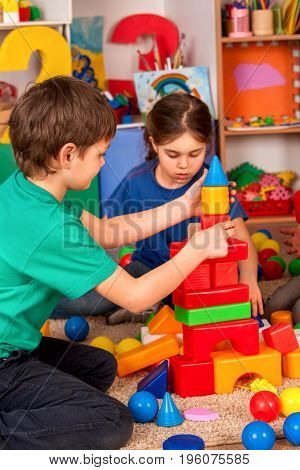 Children building blocks in kindergarten. Couple kids playing toy on floor at home. Girl was embarrassed near boy.