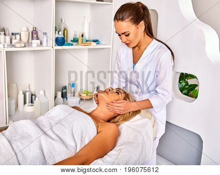 Facial massage for forty five year old woman. Portrait of woman middle-aged take face cleaning in spa salon. Interior with cosmetic background. Removing wrinkles and acne procedure number one.