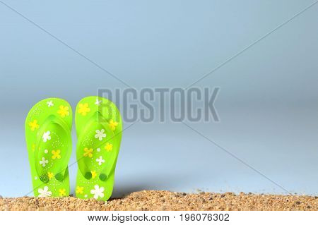 Summer background with flip flops on the sandy beach