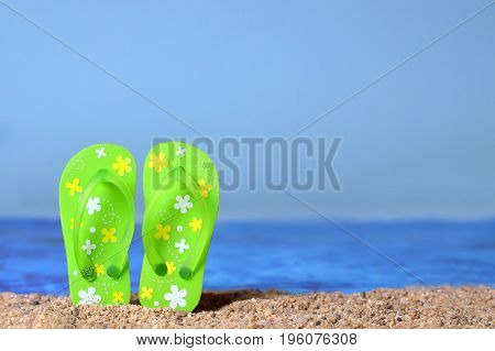 Summer concept with flip flops on the sandy beach