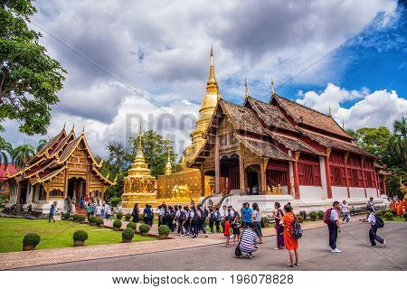 CHIANG MAI - JULY 16 2017: Tourists visitors to pray at the Phra Singh Temple in Chiang Mai Thailand. The temple founded in 1345 is a major tourist attraction in Chiang Mai.