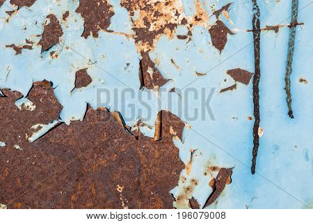 Blue paint peeling of from rusty metallic surface texture