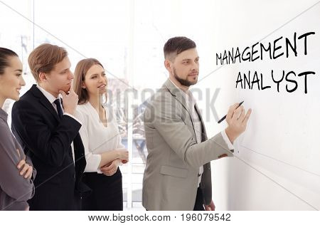 Concept of management analyst. Business trainer with team of managers at conference in office