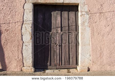 Old wooden rustic door with locks in weathered stucco wall representing old colonial Mexico in Valladolid Yucatan