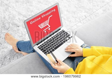 Internet shopping concept. Woman using laptop at home