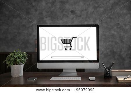 Internet shopping concept. Computer display with icon of market trolley and search bar on table at home