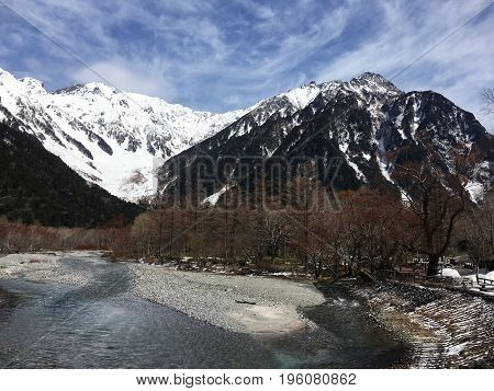 Mountains in the Kamikochi National Park and the unfrozen Azuza River in Japan